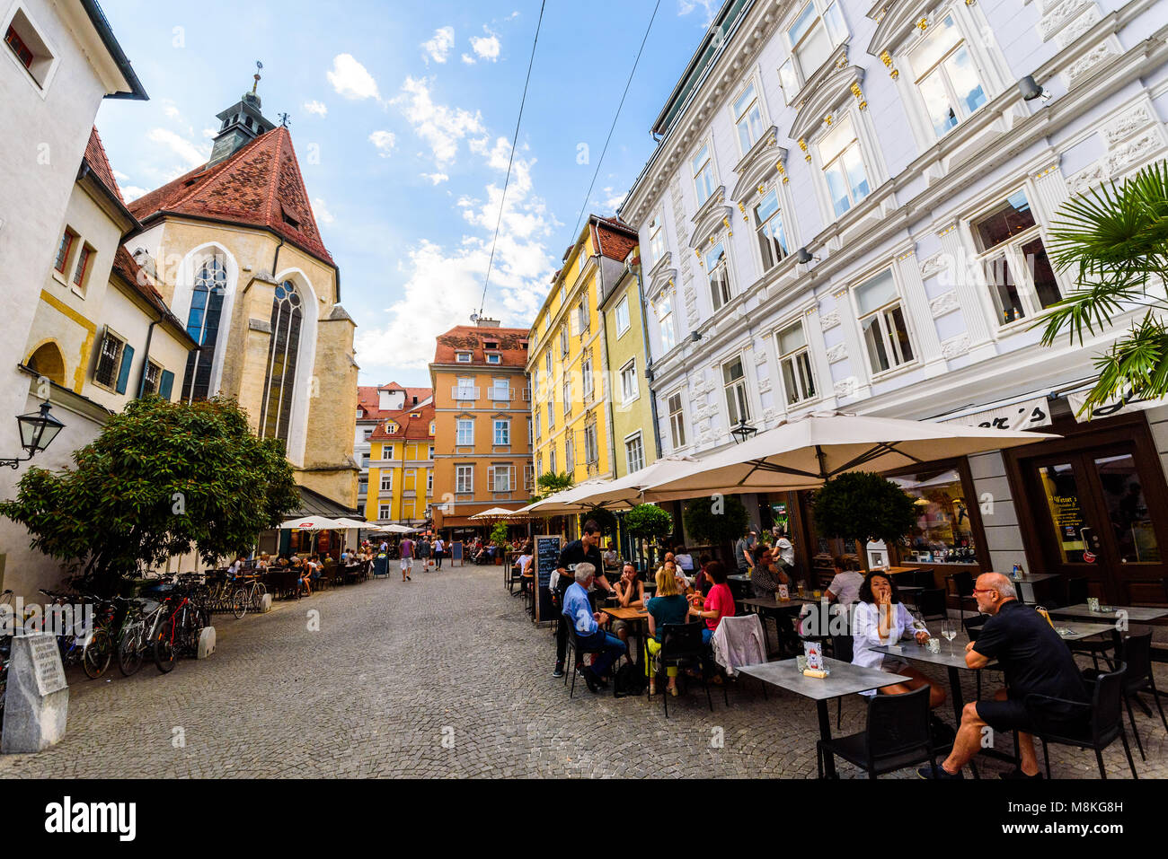 Graz, Styria / Austria - 07 09 2016 : One of colorful alleys in Graz city with historical buildings church and restaurants Stock Photo
