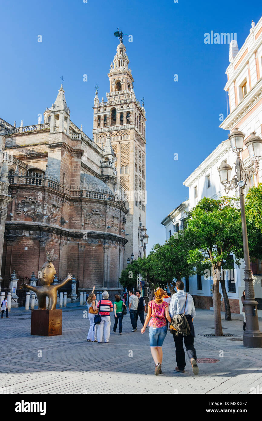Seville, Andalusia, Spain : Tourists walk towards the Gothic Cathedral and Giralda bell tower in Plaza del Triunfo - Stock Image