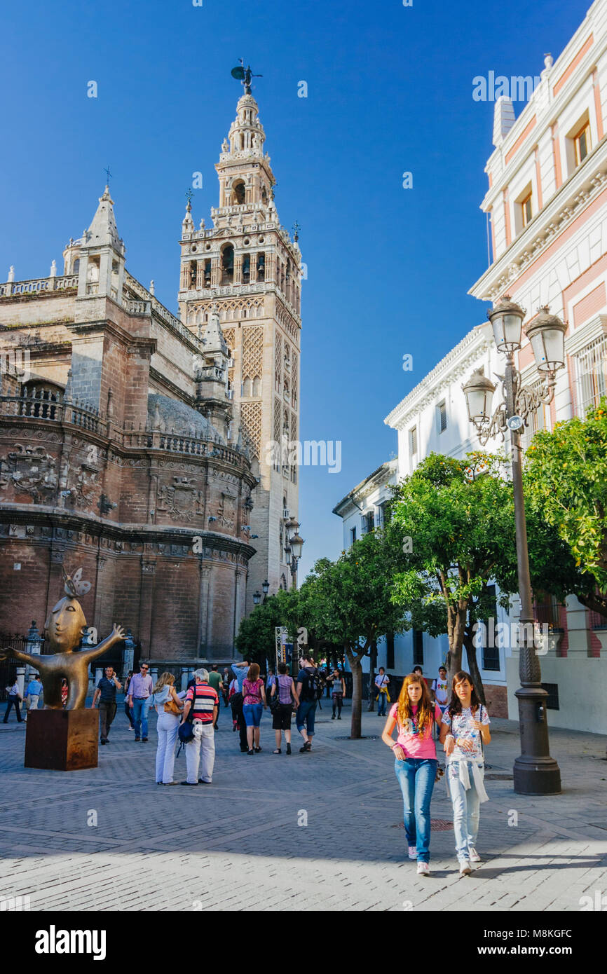 Seville, Andalusia, Spain : People walk past the Gothic Cathedral and Giralda bell tower in Plaza del Triunfo square. - Stock Image