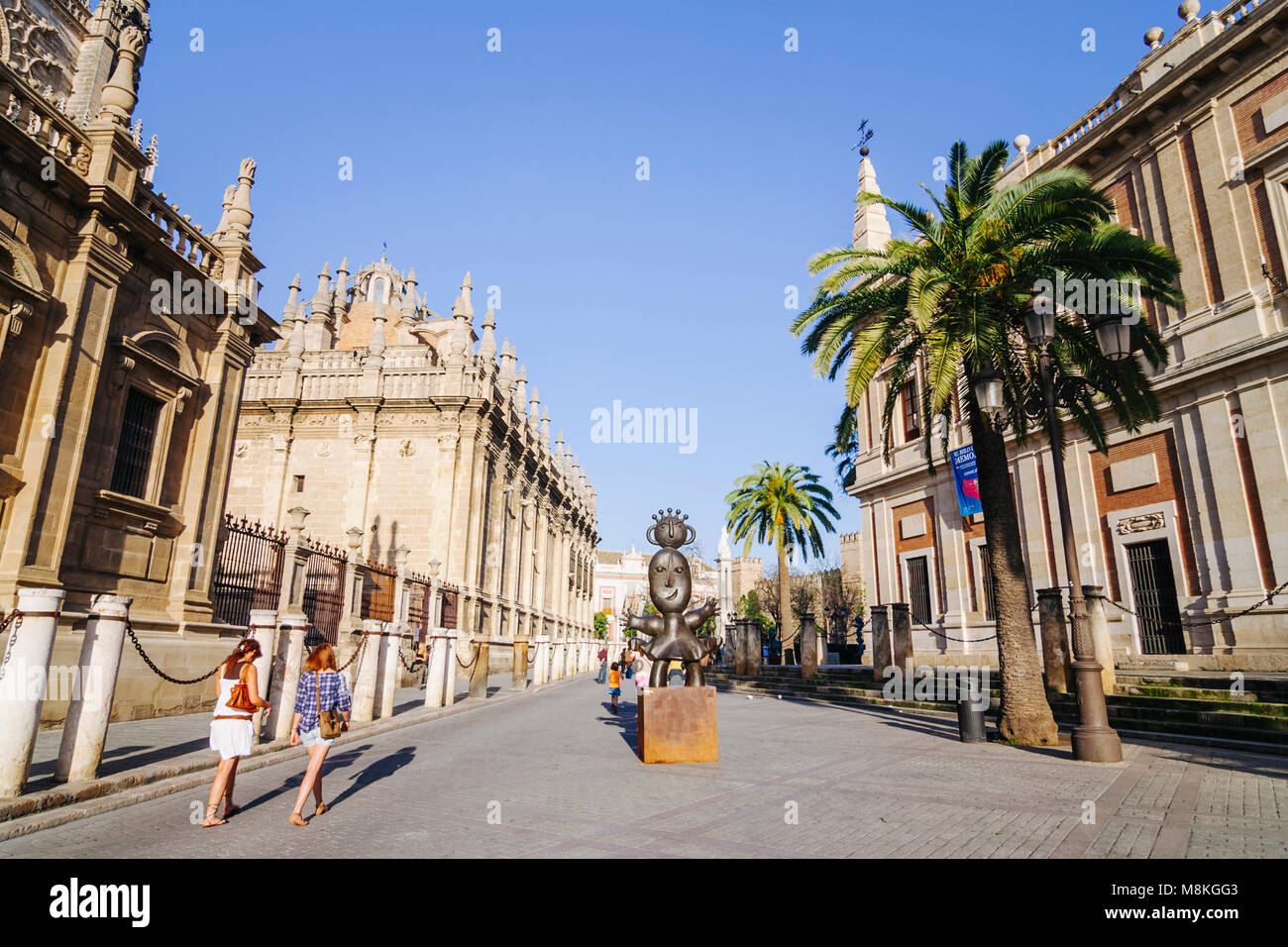 Seville, Andalusia, Spain : Tourists walk past the Unesco listed Cathedral of Seville, the largest Gothic structure - Stock Image