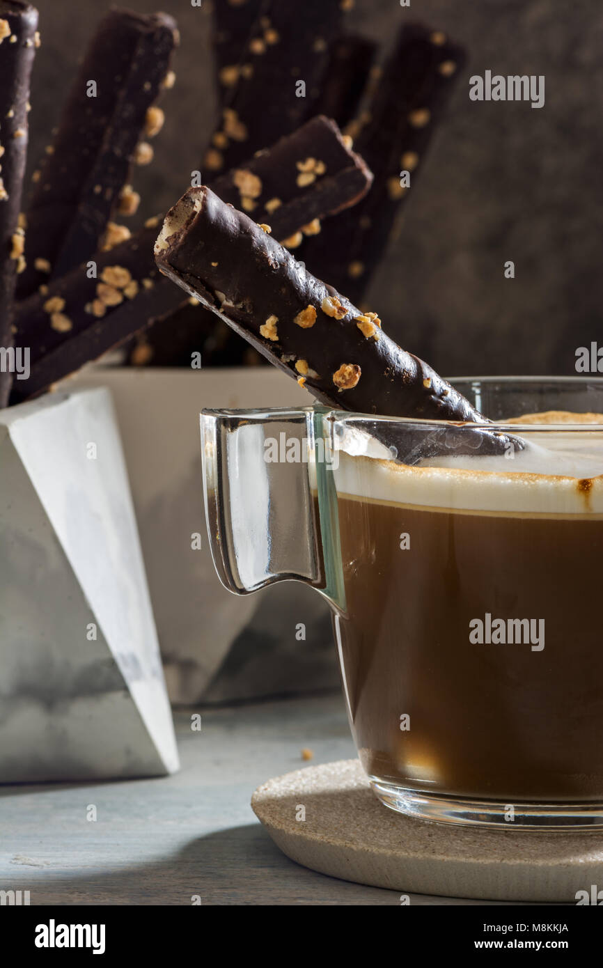 Cappuccino and wafer Chocolate Rolls with almonds, on stone dish, grunge background. - Stock Image