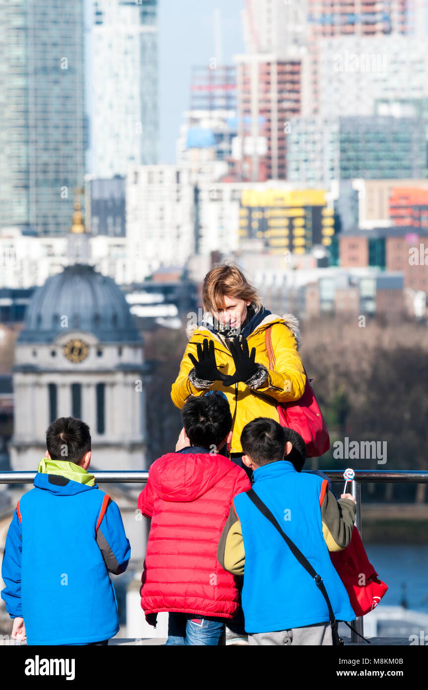 A school party,  at Greenwich Park looking at building work on the Isle of Dogs. - Stock Image