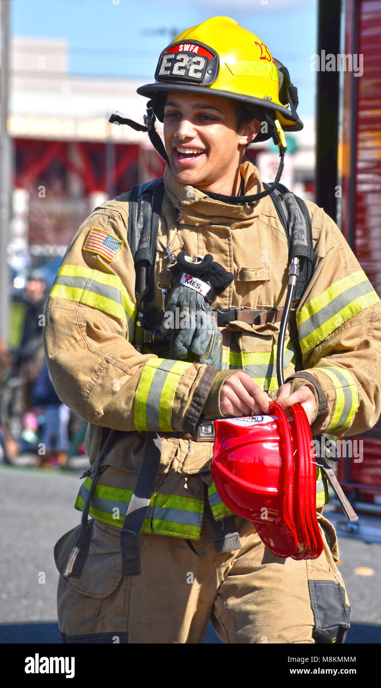 A fireman in the St. Patrick's Day Parade in Bellingham, Washington on March 17, 2018.  The fireman is giving - Stock Image