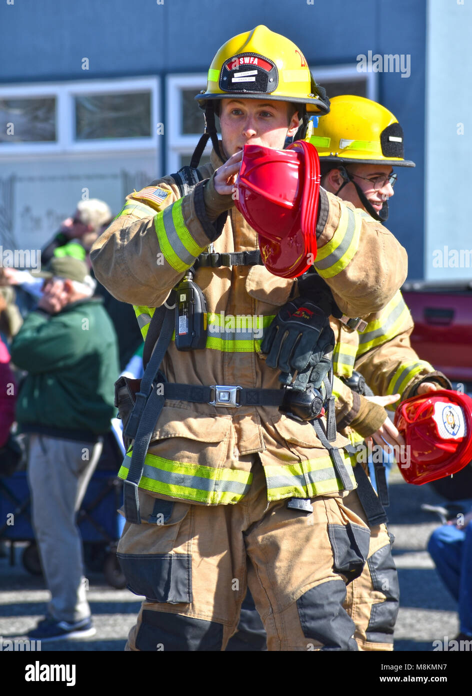 Firemen giving out hats at the Bellingham, Washington, St. Patrick's Day Parade on March 17, 2018. - Stock Image