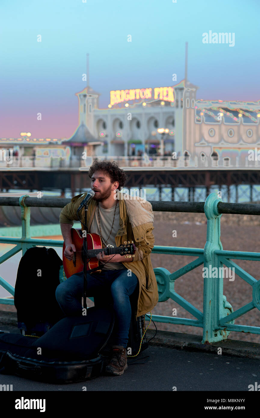A busker entertains passersby with songs and guitar on the promenade near the famous Brighton Pier, one of the UK's - Stock Image