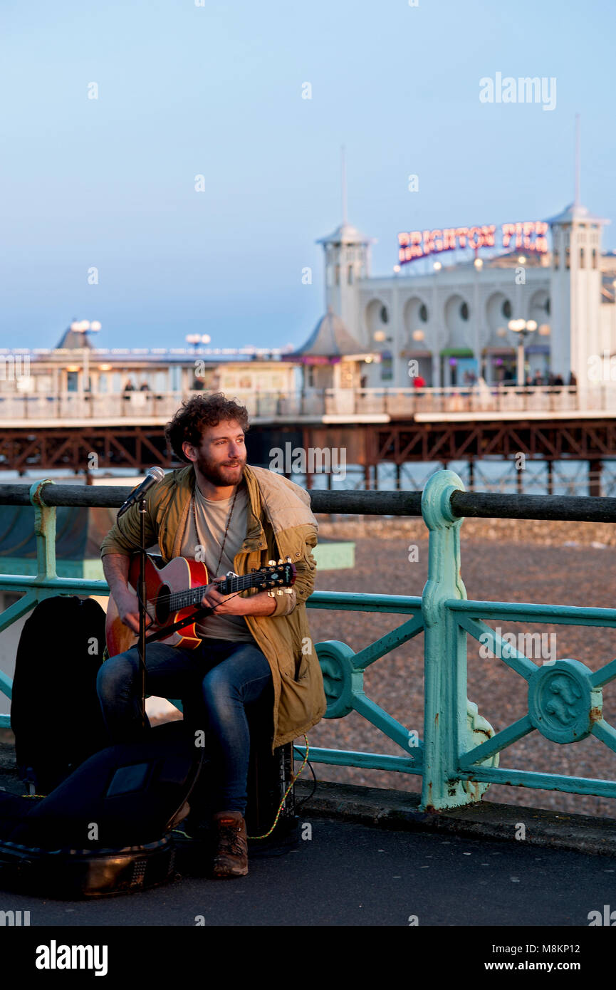 A busker entertains passersby with songs on Brighton's promenade near the famous Brighton Pier, one of the UK's - Stock Image