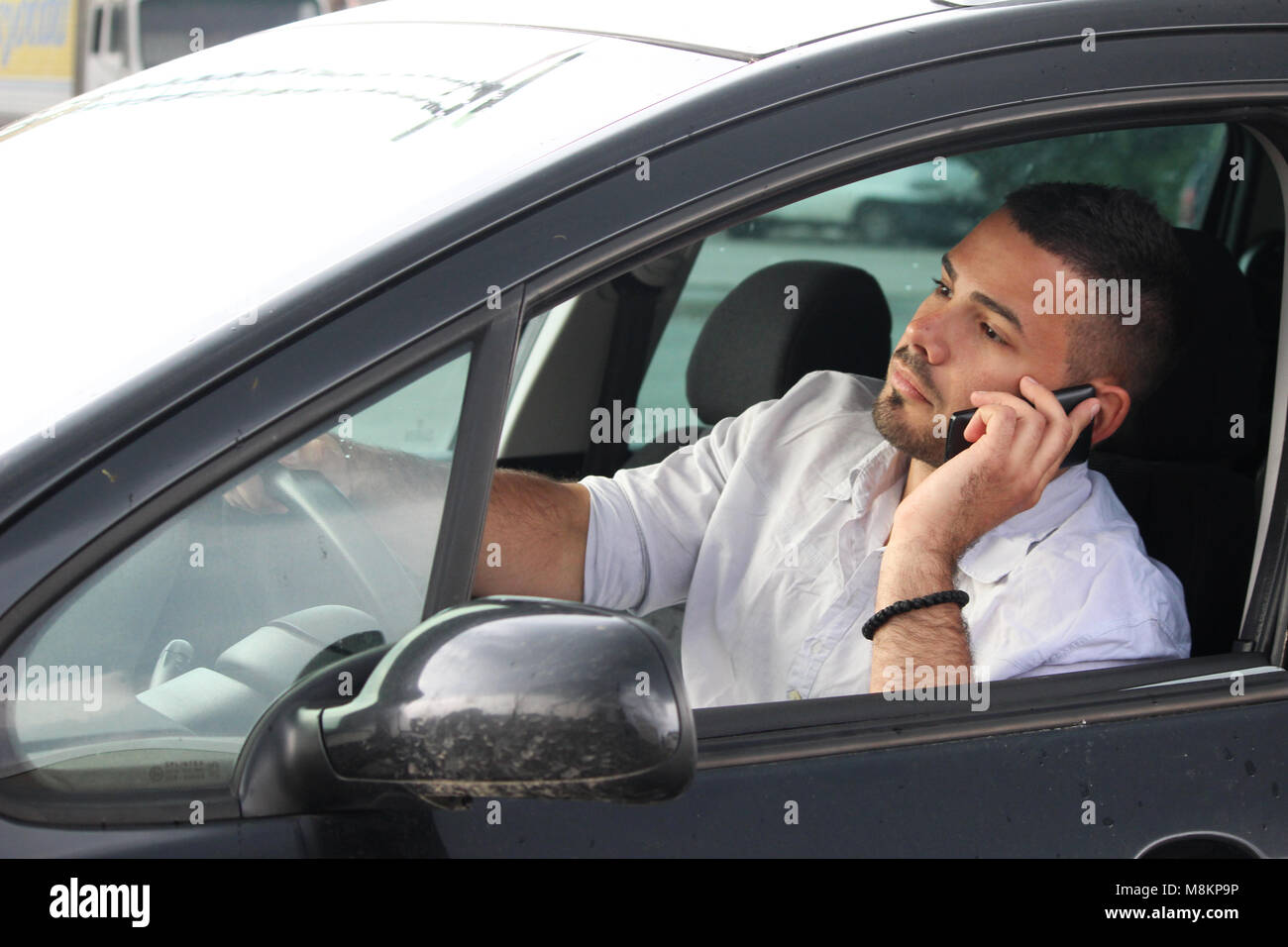 attention sleepy man drivin and speaking at phone - Stock Image