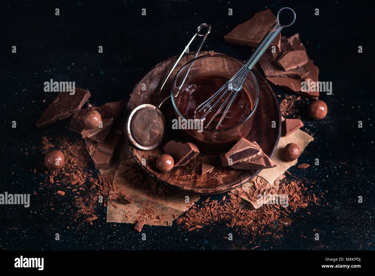 Chocolate glazing in a glass cup with a whisk. Chocolate chunks with cocoa powder, cinnamon and other spices on - Stock Image
