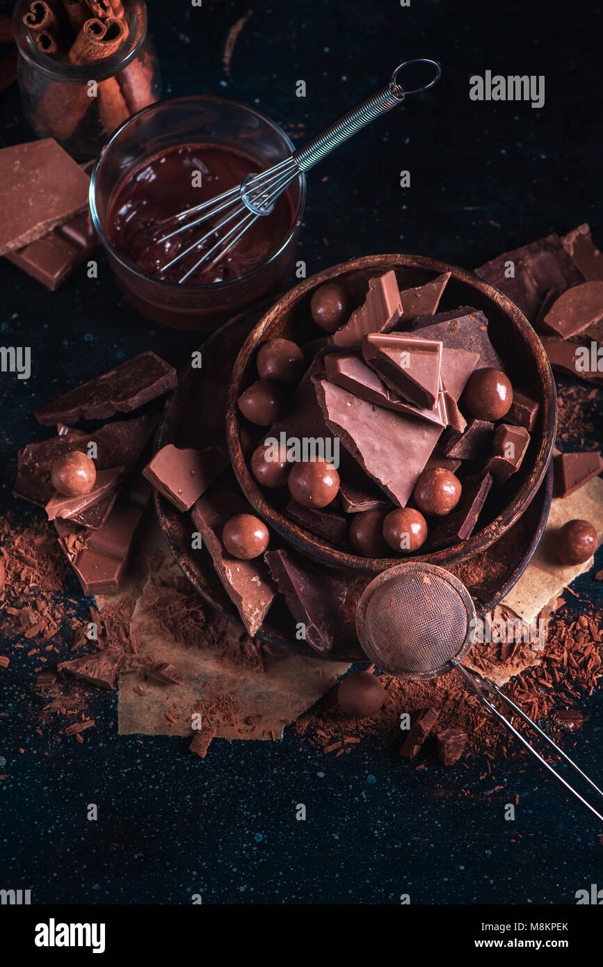 Wooden bowl with homemade chocolates and chocolate pieces, glazing with a whisk, scattered cocoa powder on a dark - Stock Image