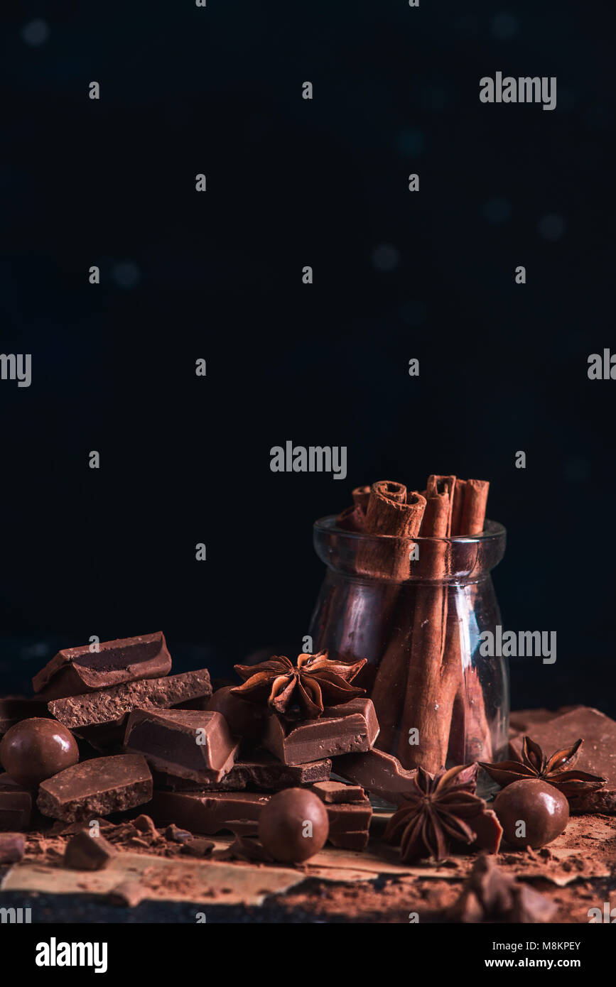 Dessert ingredients close-up. Cinnamon in a glass jar, scattered cocoa powder and pieces of broken chocolate on - Stock Image