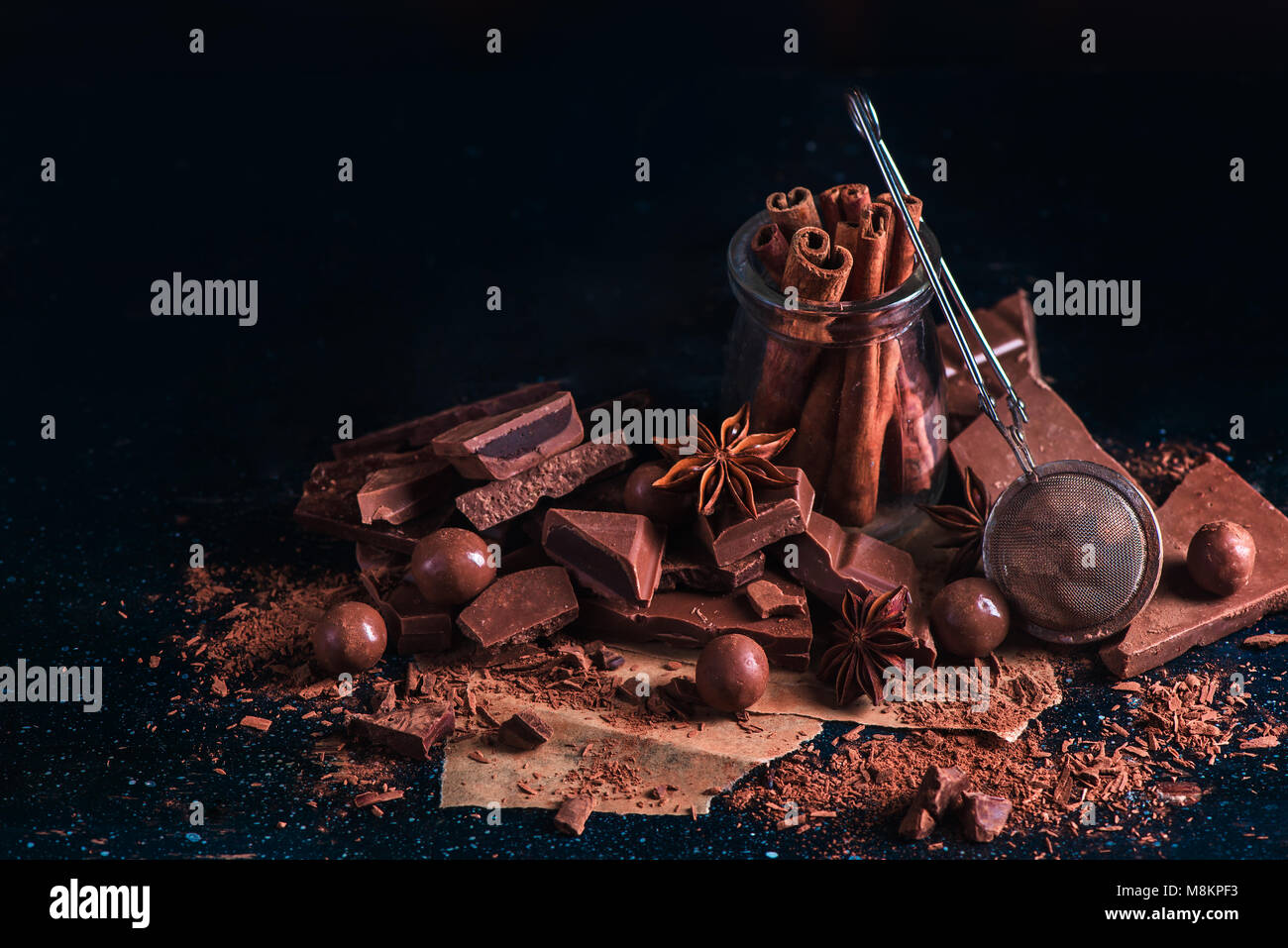 Header with cinnamon in a glass jar, scattered cocoa powder and pieces of broken chocolate on a dark background - Stock Image