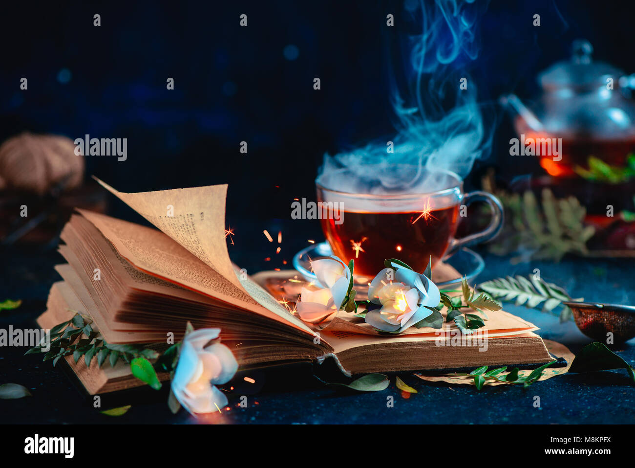 Steaming cup of tea on an open book with magical burning flowers. Fantasy reading concept. Dark still life with - Stock Image