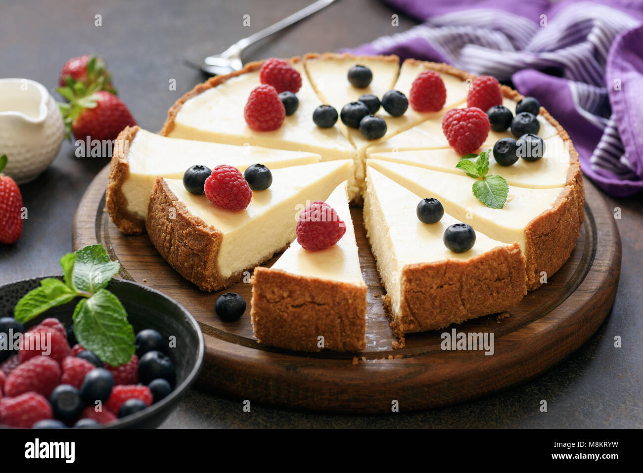 Classic plain New York Cheesecake sliced on wooden board, closeup view, selective focus Stock Photo
