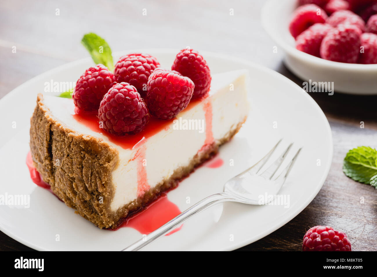 Cheesecake with raspberries and berry sauce on white plate, closeup view, selective focus. Slice of cheesecake - Stock Image