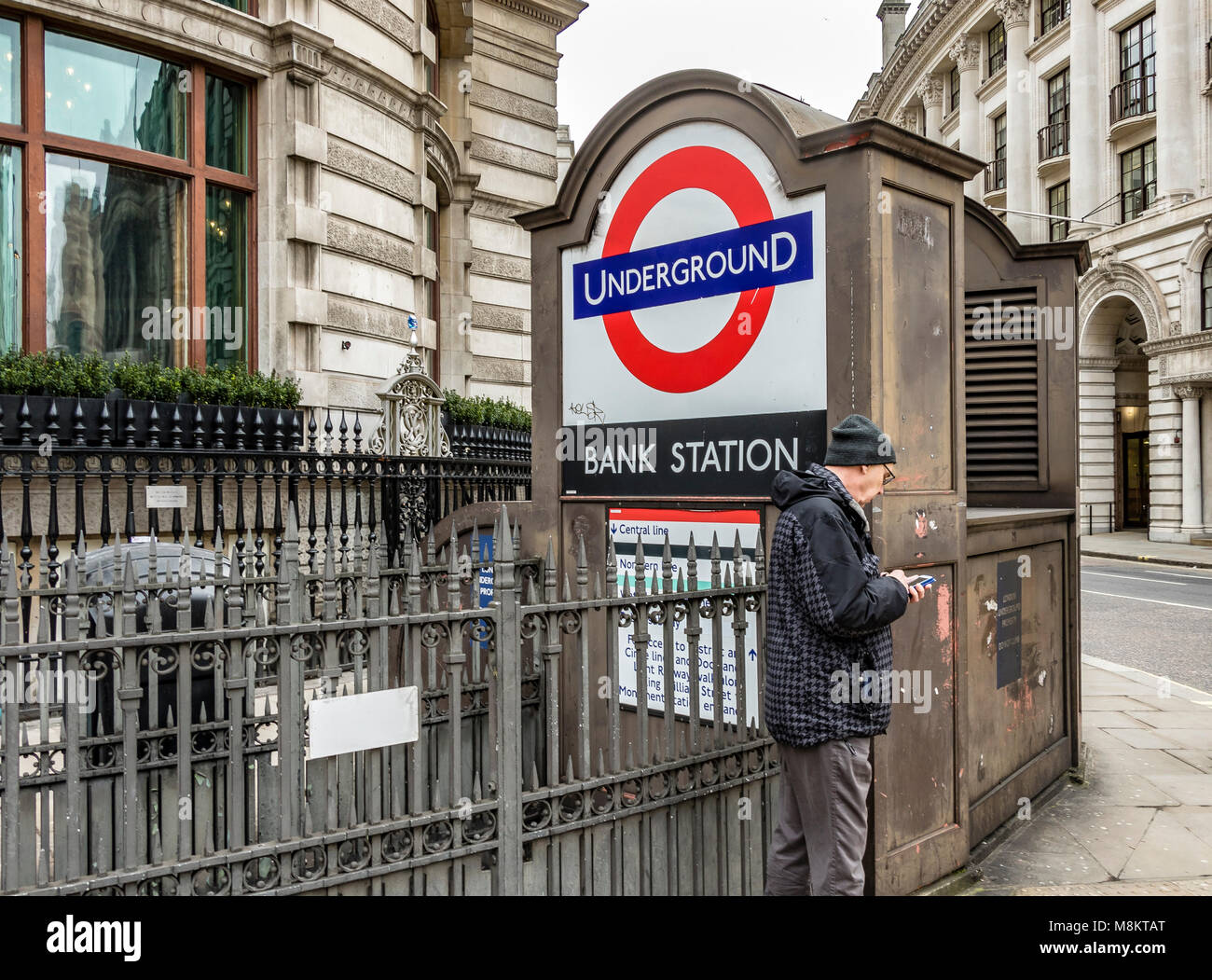 Man looks at his phone outside Bank Station entrance in The City Of London - Stock Image