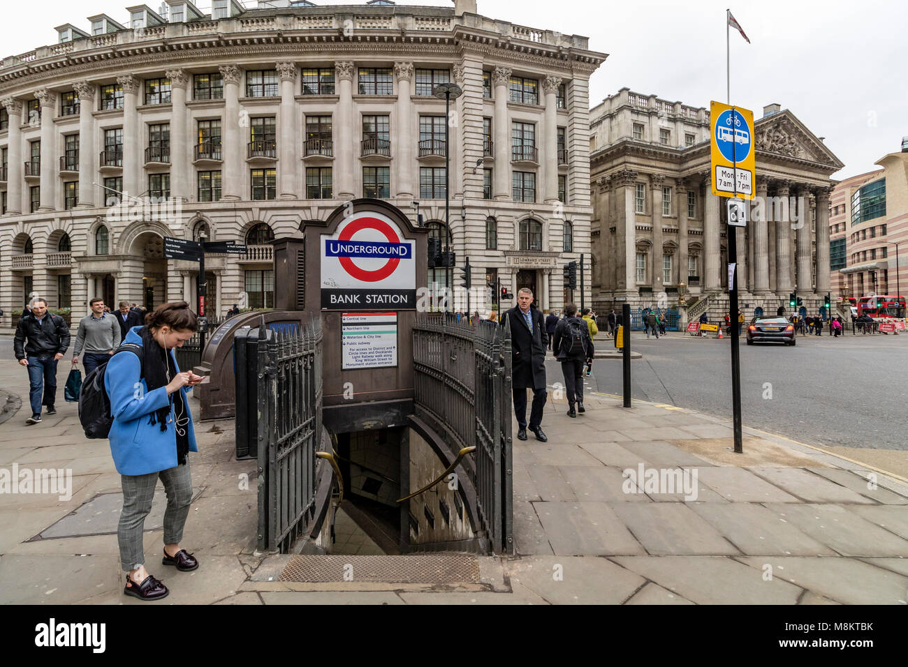 A woman checking her phone outside Bank Tube station entrance in The City Of London - Stock Image