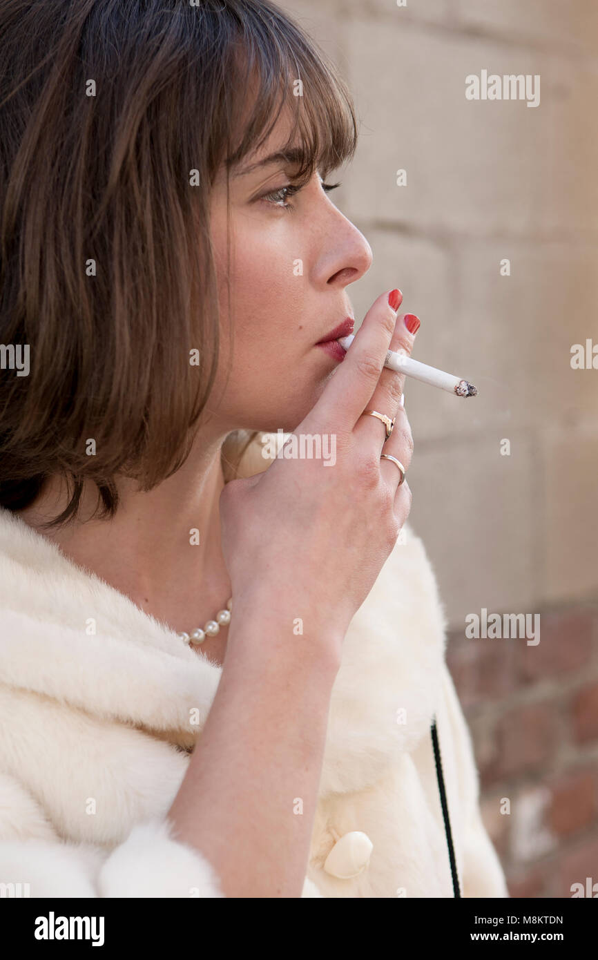 Woman with red lipstick, wearing a pearl necklace, smoking a cigarette.Stock Photo
