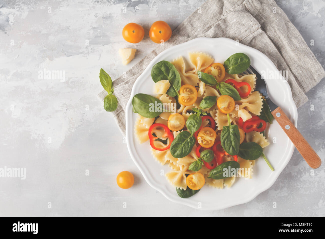 Italian pasta farfalle salad with vegetables, basil and spinach in a white plate. Light background - Stock Image