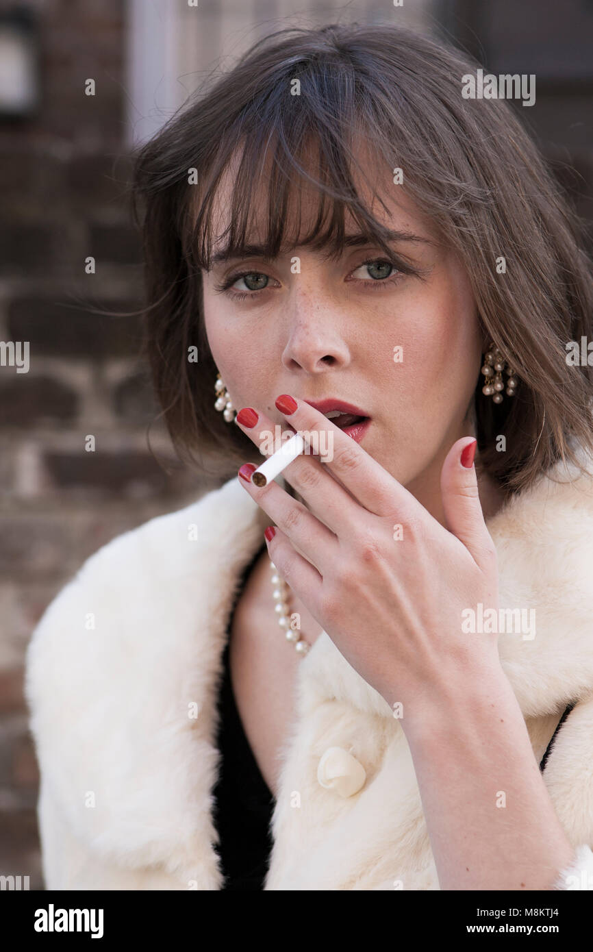 A well dressed woman wearing red lipstick and a pearl necklace, with an unlit cigarette in her lips. - Stock Image