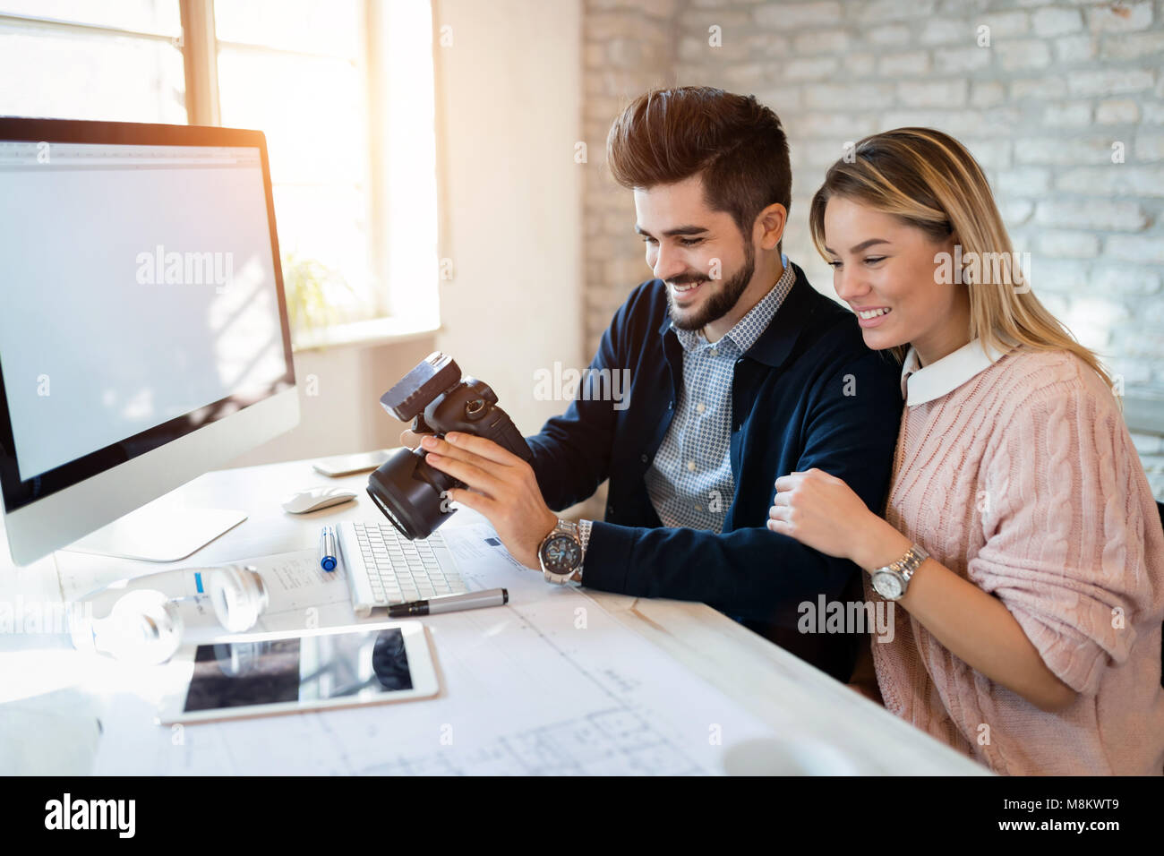 Picture of young attractive designers looking at camera - Stock Image