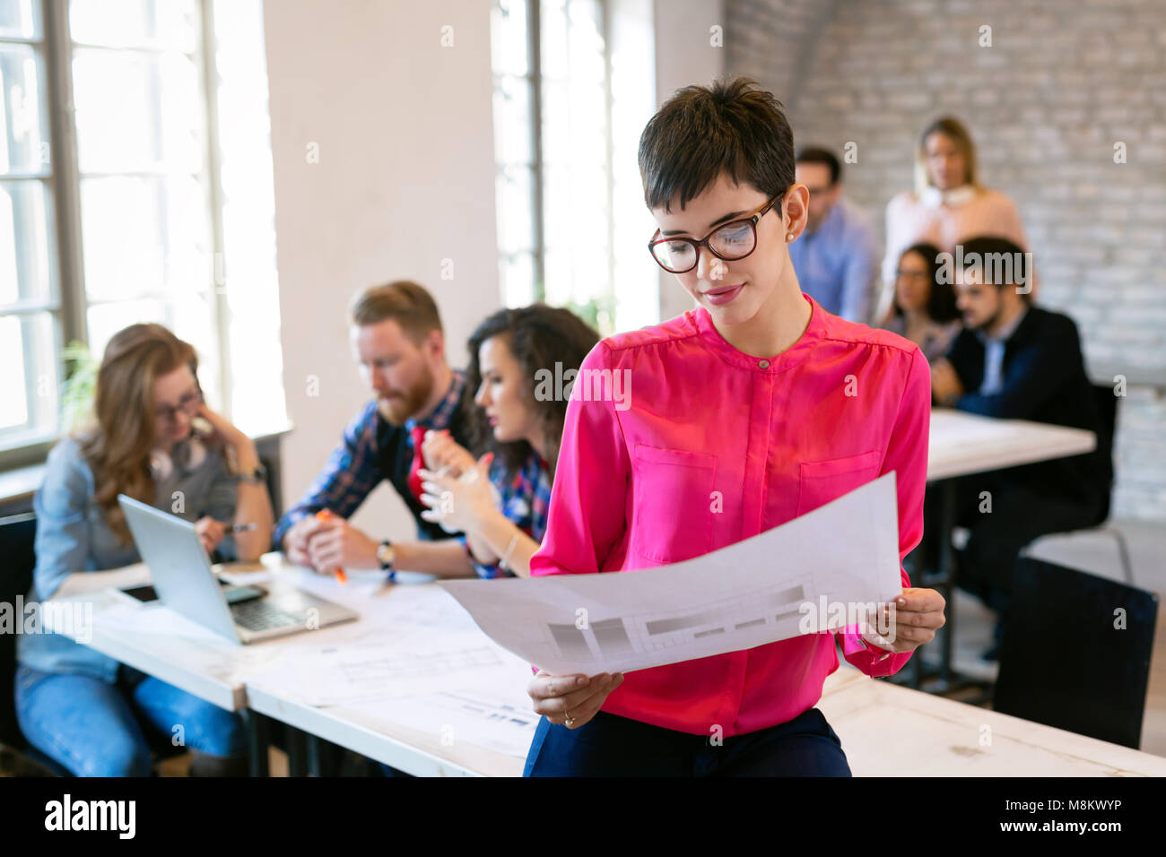 Group of young perspective architects looking at project papers Stock Photo