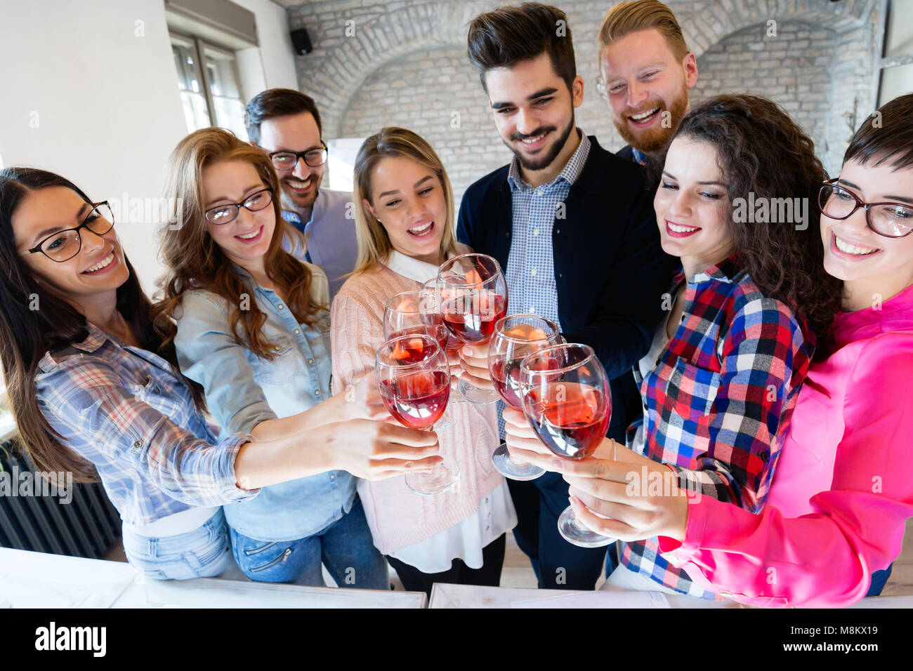 Office colleagues celebrating achievement of company goals - Stock Image