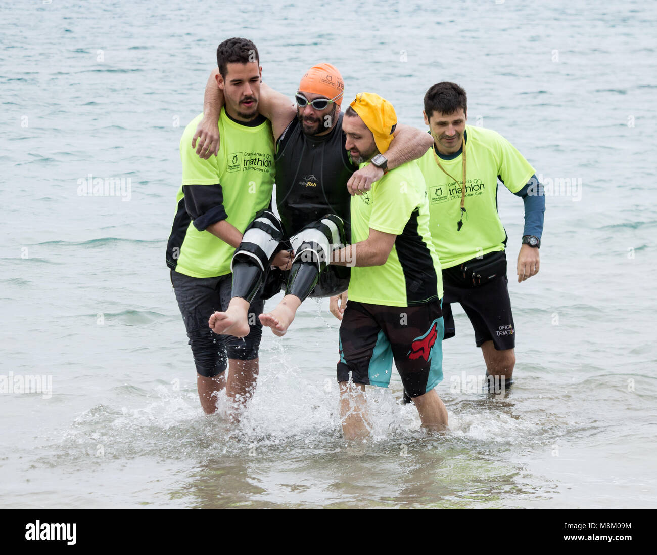 A disabled triathlete is helped out of the water after completing the swim leg of the sprint triathlon at the ETU - Stock Image