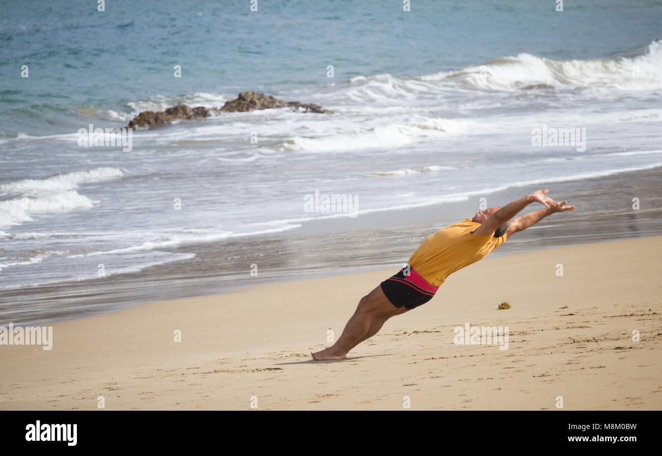 A man appears to be defying gravity as he is photographed mid somersault on a beach in Spain. Stock Photo