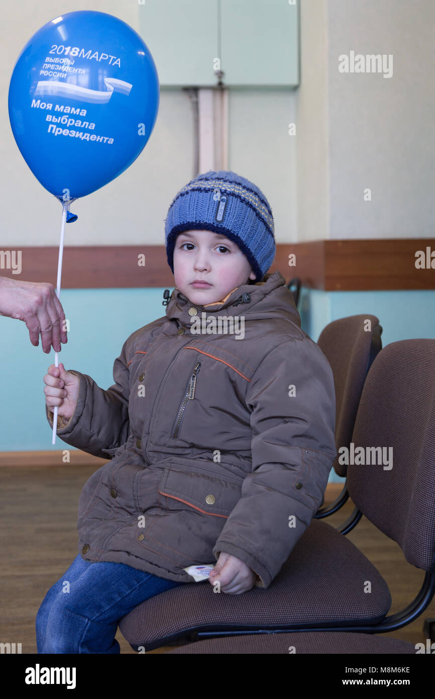 MOSCOW, RUSSIA - MARCH 18, 2018: A baby is given a balloon after his mother voted in the presidential election of - Stock Image