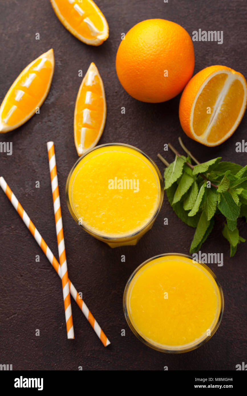 Two glasses of freshly squeezed orange juice and mint on a dark brown background. Top view - Stock Image
