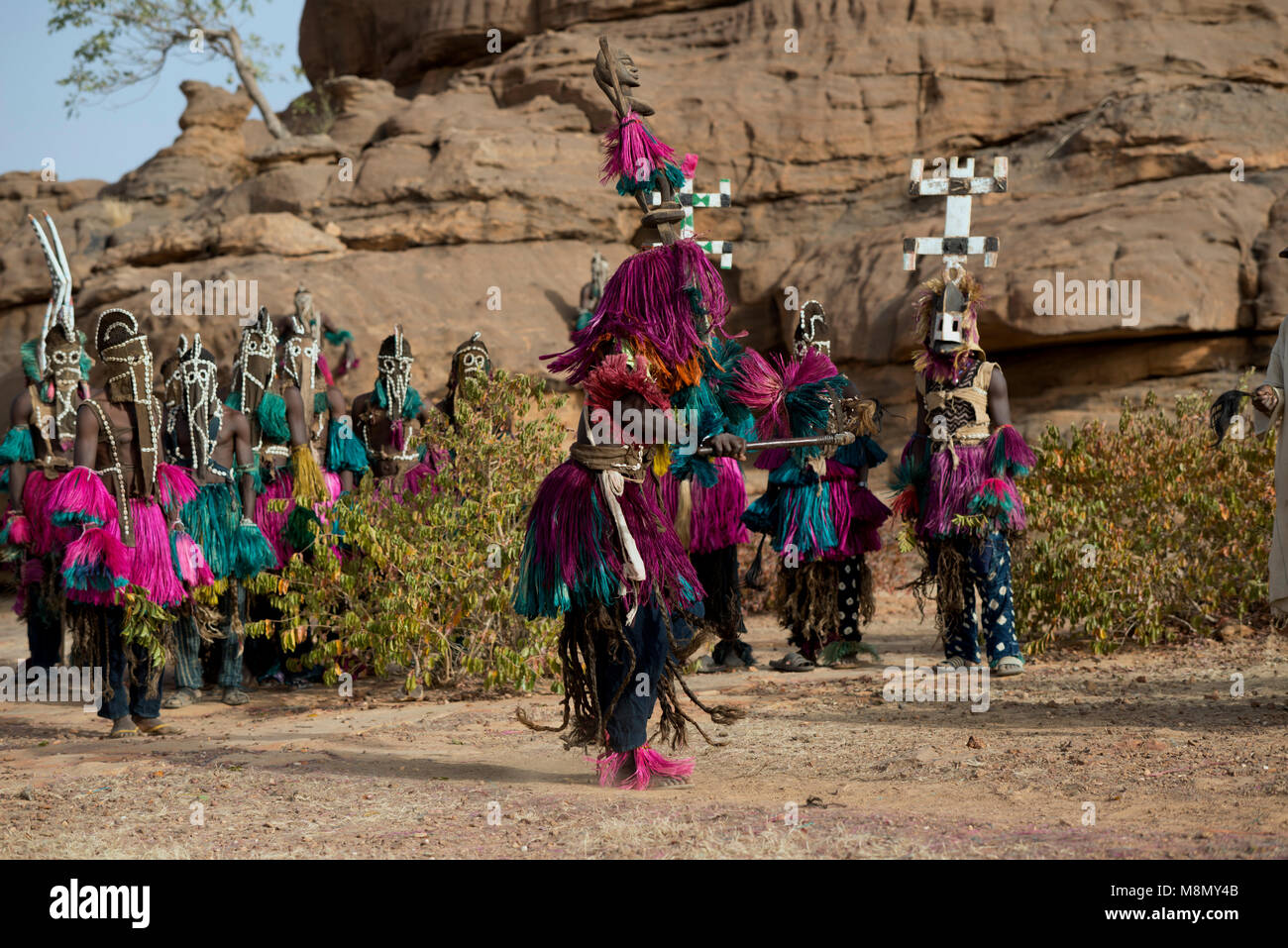 A Dogon masked dancer shaking a stick during a ritualistic tribal dance. Dogon country, Mali, West Africa. - Stock Image