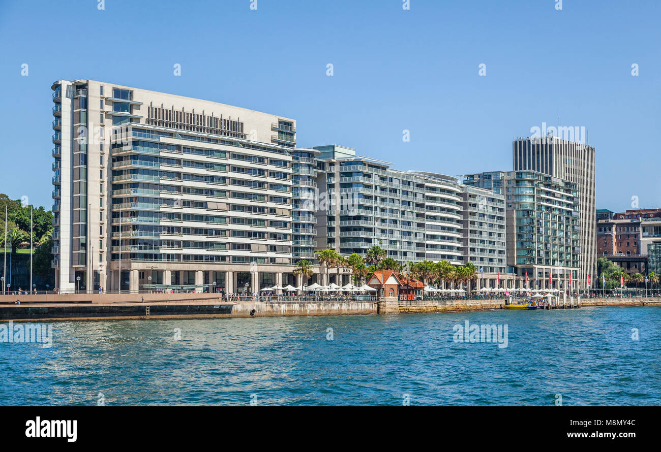 view of East Circular Quay on Sydney Cove with colonaded shops and restaurants, the Colonial Peninsula and Mirvac - Stock Image