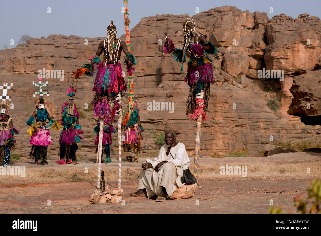 Dogon masked dancers on stilts tower over the village chief at the conclusion of a ritual tribal dance. Dogon country, - Stock Image