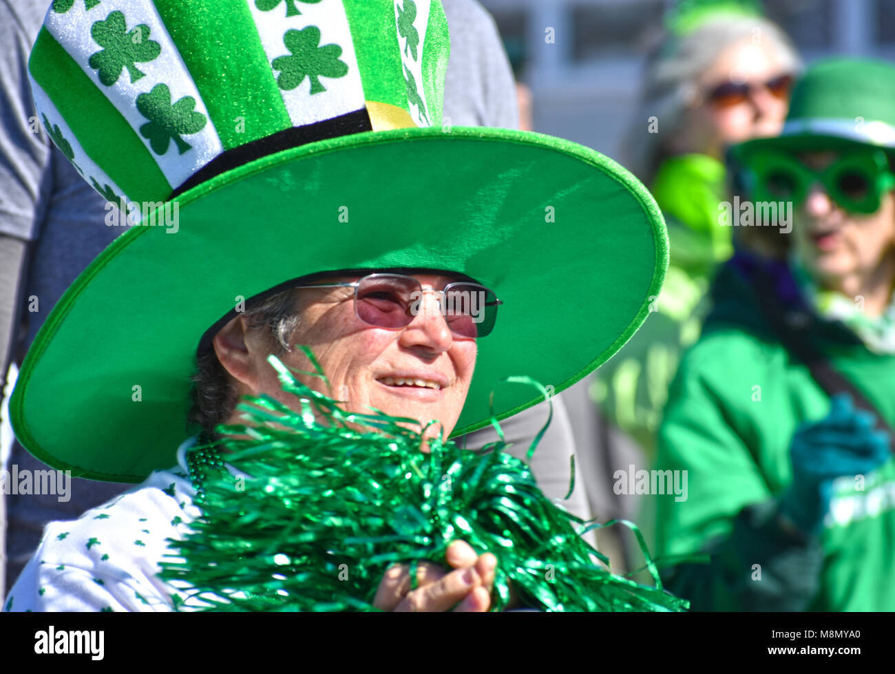 An older woman wearing a large green hat with shamrocks on it at the Bellingham, Washington St. Patrick's Day - Stock Image