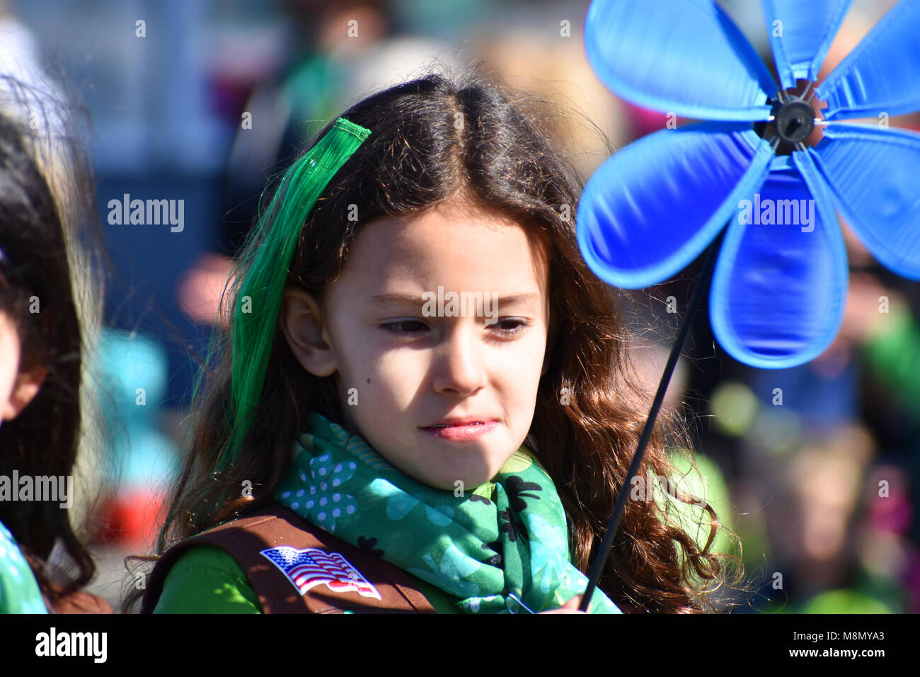 A young girl scout in the Bellingham, WA. St. Patrick's Day Parade on March 17, 2018.  A U.S. flag patch is - Stock Image