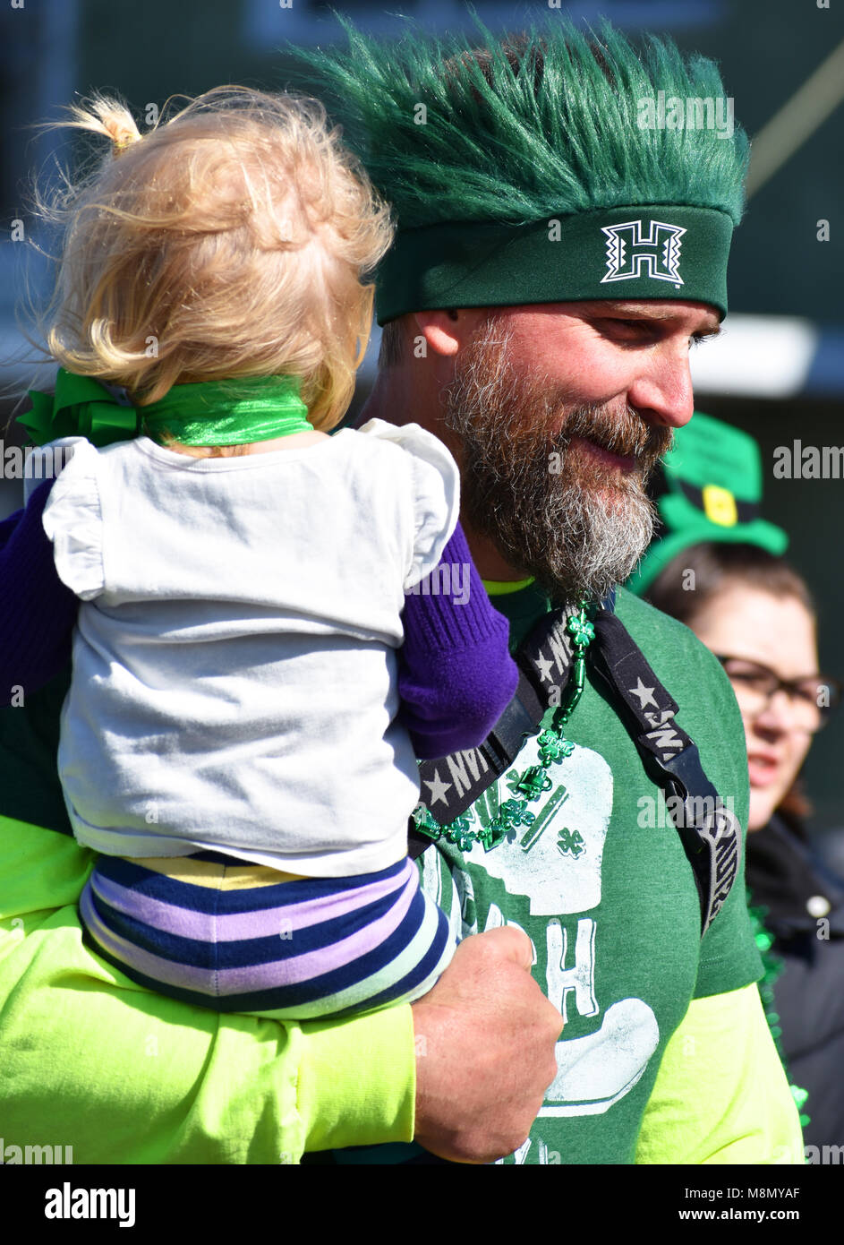 Man holding his young daughter while walking in the Bellingham, Washington St. Patrick's Day Parade on March - Stock Image