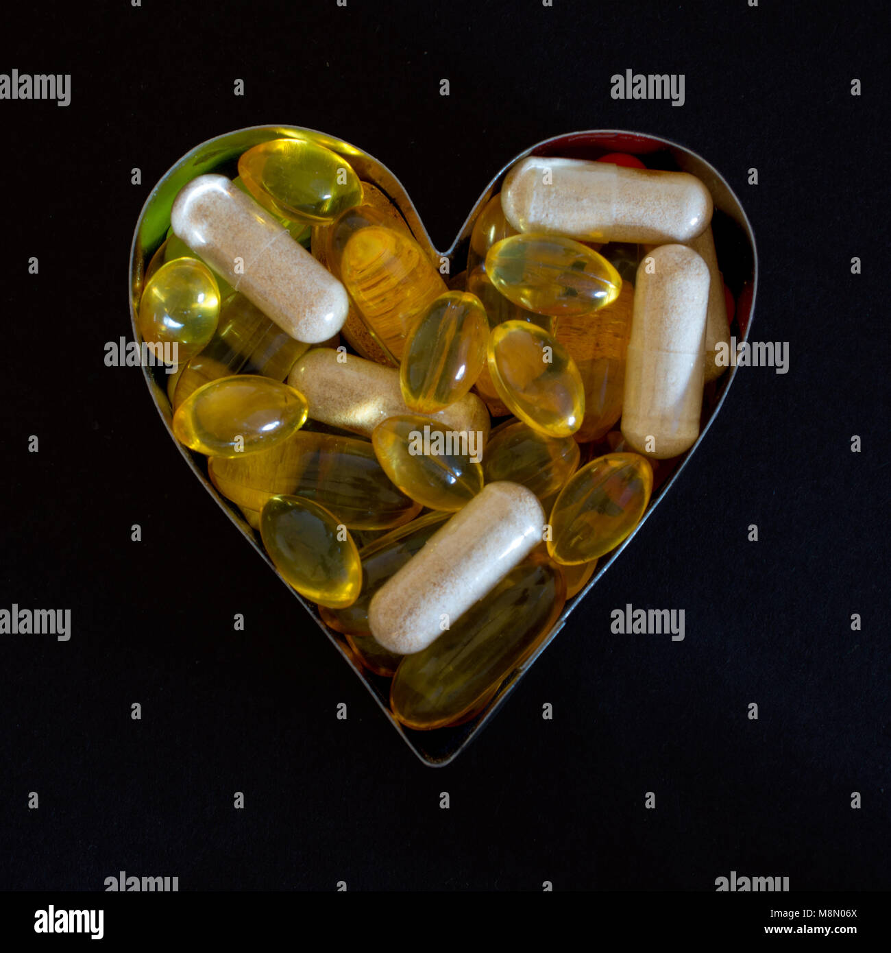 Dietary supplements in heart-shaped cookie cutter isolated against black background - Stock Image