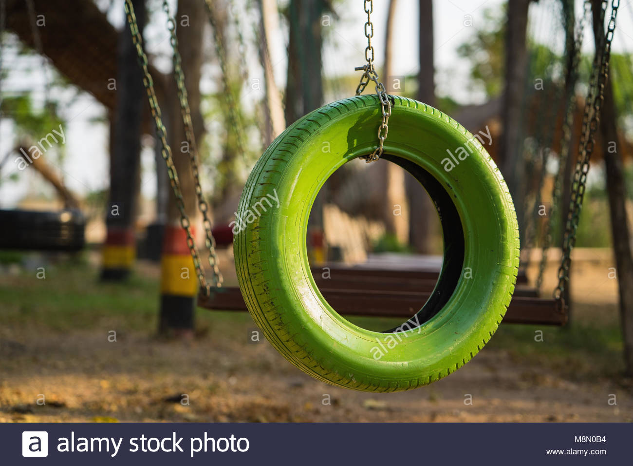 Color old car tire hanging on tree at playground Stock Photo ...