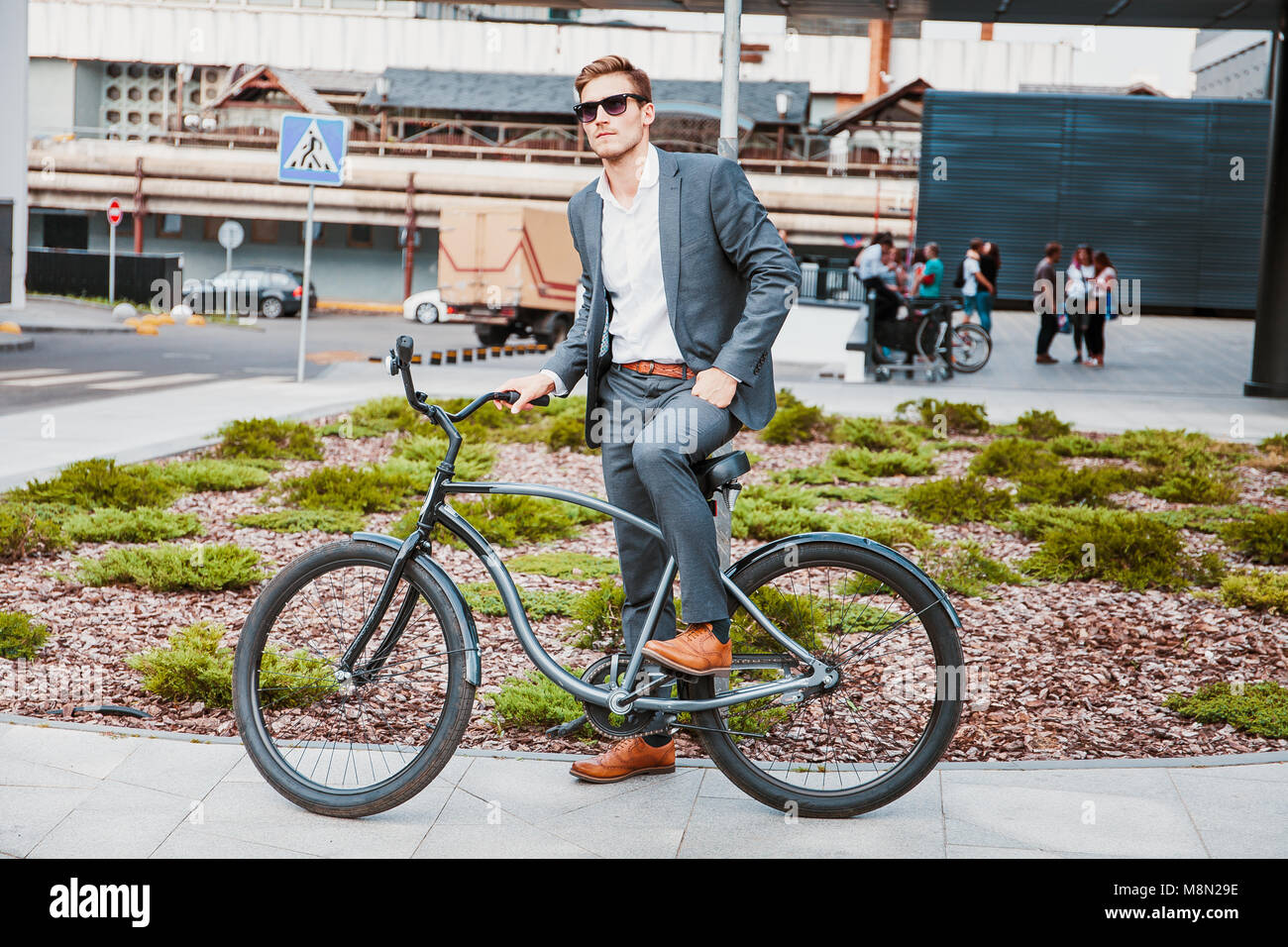 Businessman riding bicycle to work on urban street in morning - Stock Image