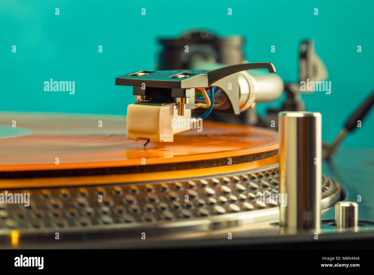 Closeup of turntable needle on spinning orange colored vinyl record - Stock Image