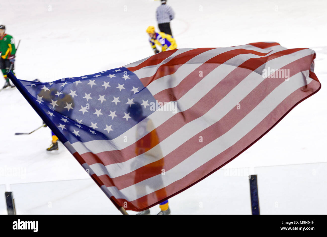 USA flag waving against a defocused hockey game background. - Stock Image