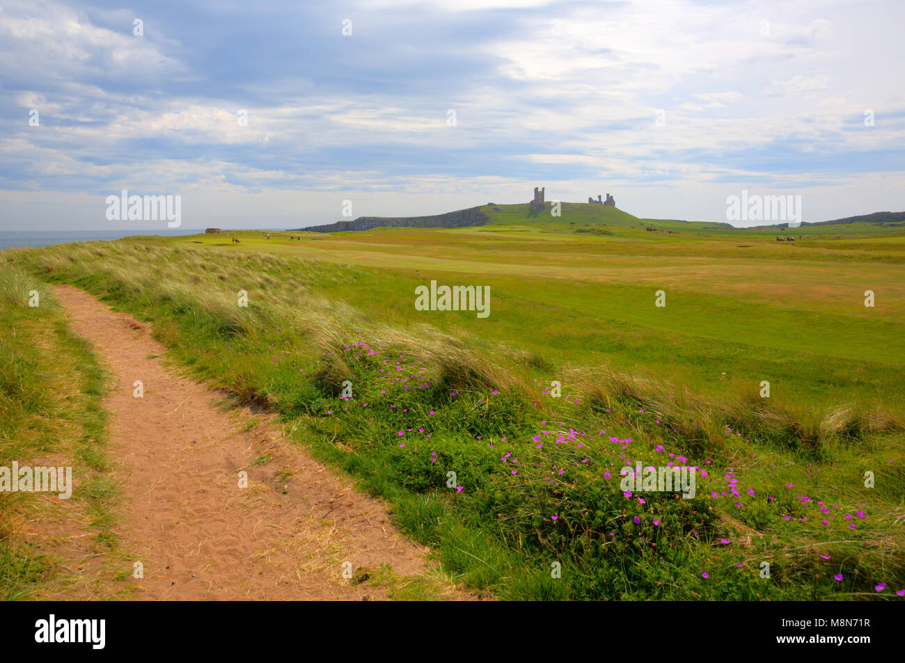 Dunstanburgh Castle Northumberland North East England with coast path - Stock Image