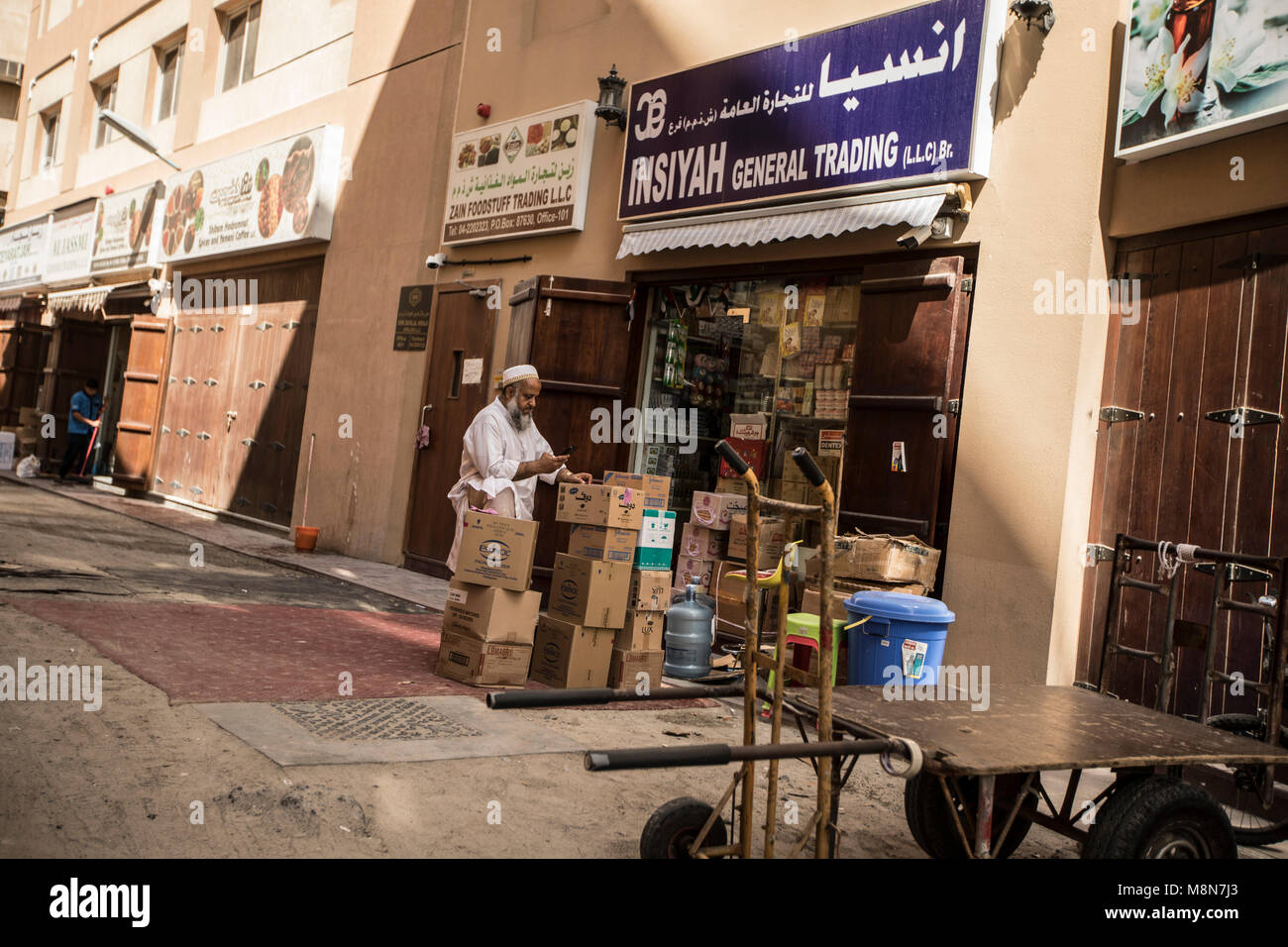 Man with goods in front of a general trading store on the street of