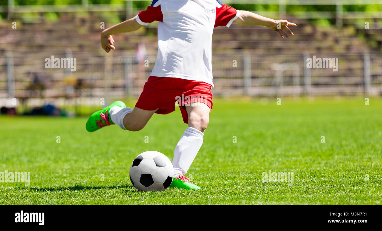 Youth Football Soccer Player Hits a Ball. Footballer Kicking Ball on Grass Pitch - Stock Image