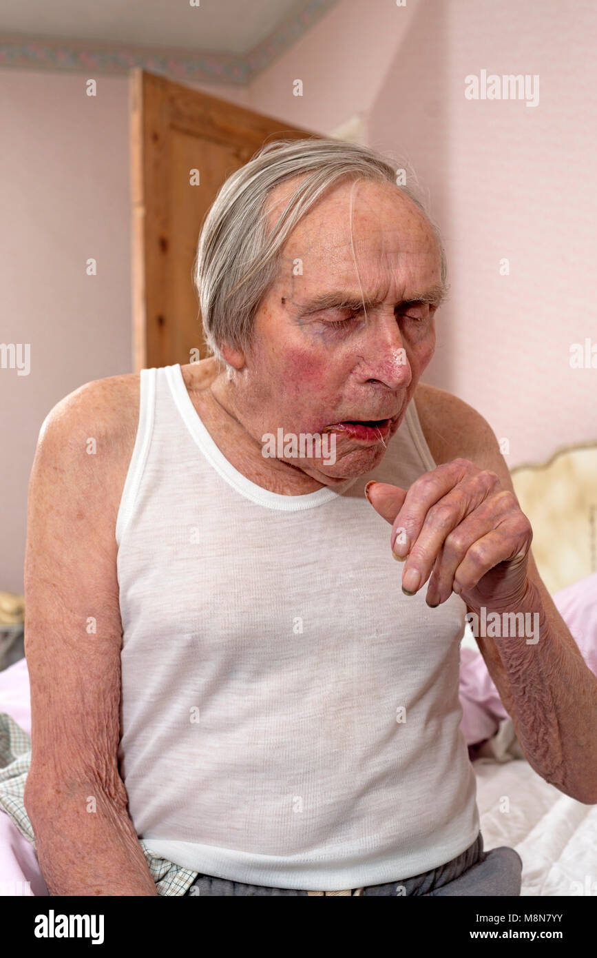 Elderly man suffering from a heavy winter cold - Stock Image