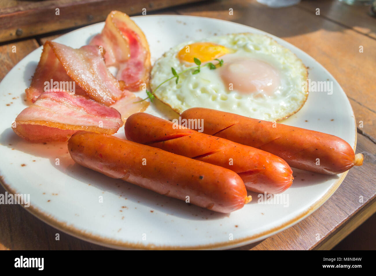 Set of american breakfast with bacon, fried eggs and sausage on wood table background Stock Photo