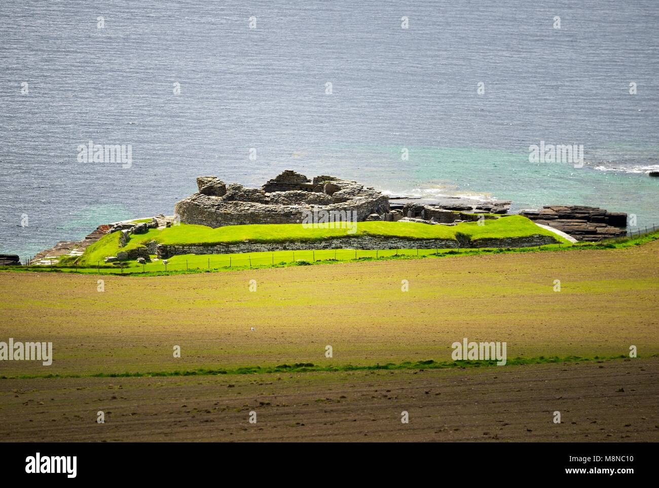 Midhowe Iron Age broch and village archaeological site on island of Rousay. Looking SW to Eynhallow Sound, Orkney, - Stock Image