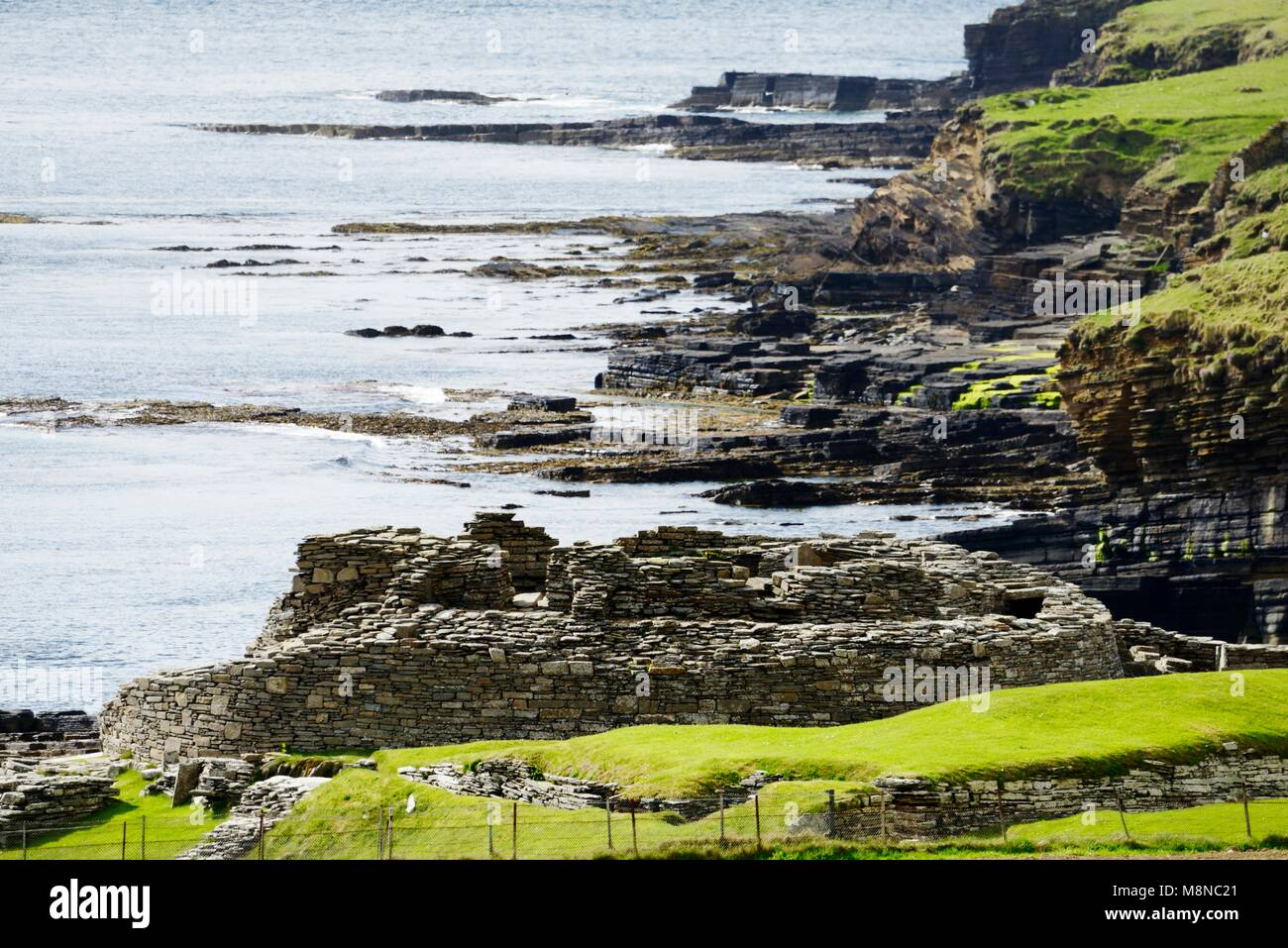 Midhowe Iron Age broch and village archaeological site on island of Rousay. Looking W along Eynhallow Sound, Orkney, - Stock Image