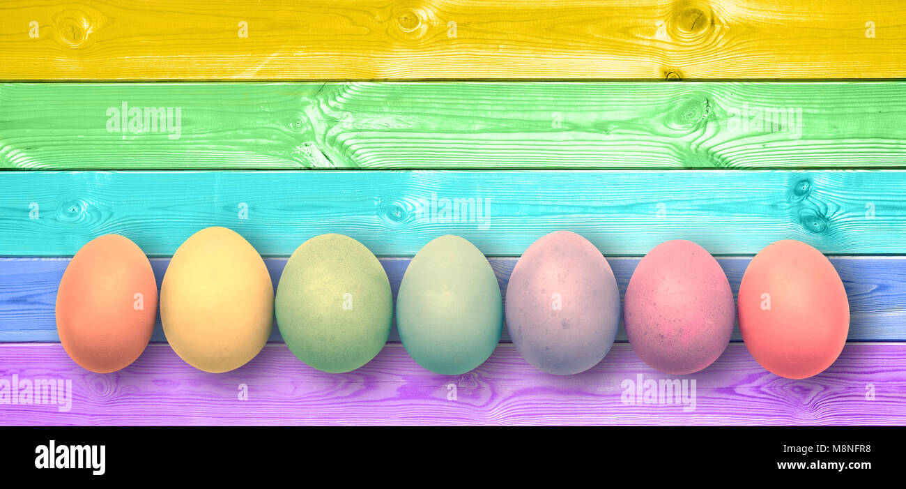 Pastel colorful rainbow painted eggs, panoramic wooden planks, easter background - Stock Image