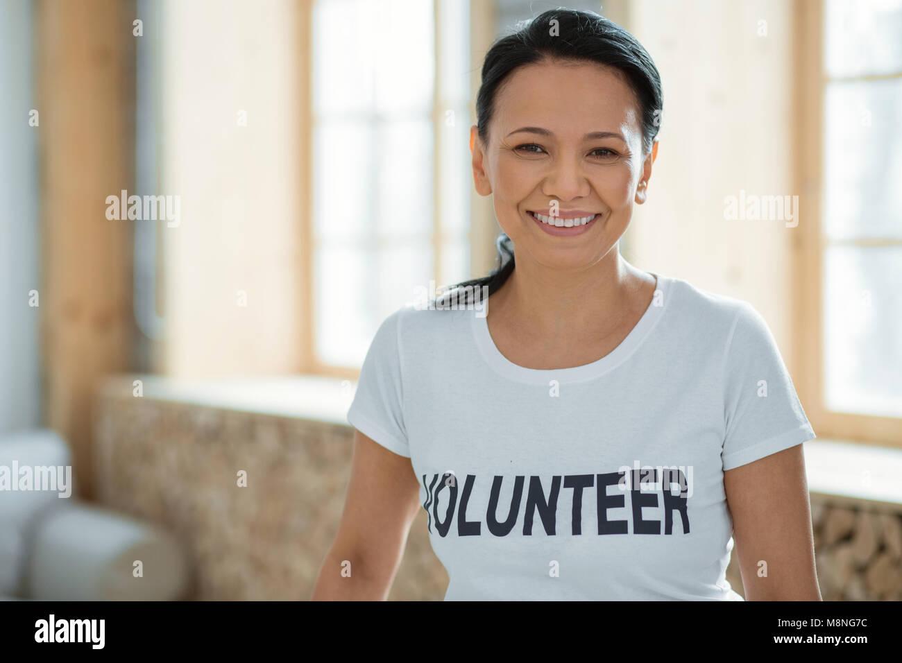 Cheerful female volunteer performing community service - Stock Image